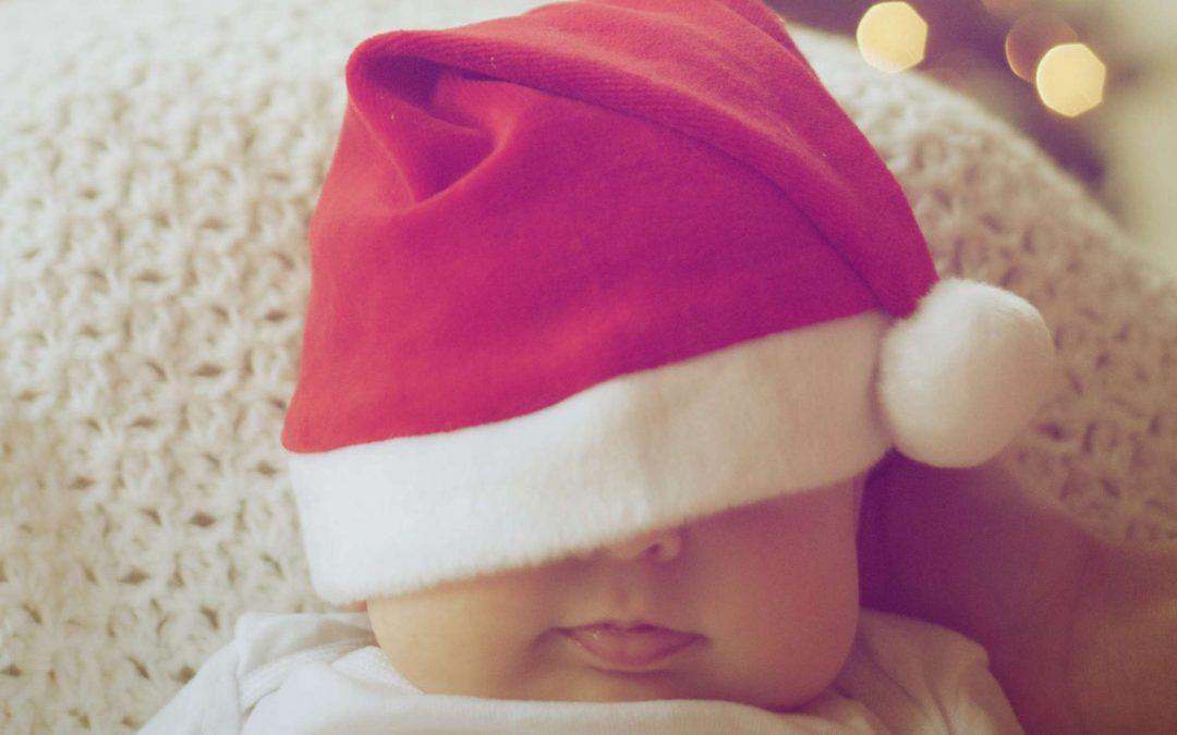 A baby sleeping under a santa hat